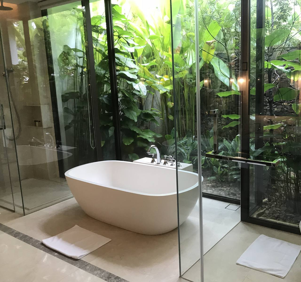free standing bath sits aside a glass wall behind which is a luxurious garden