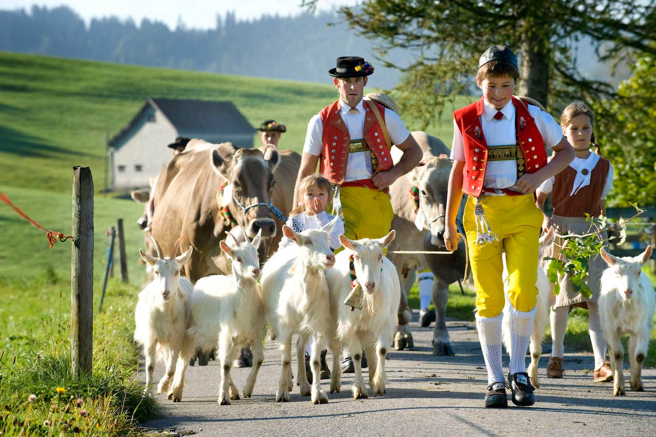 Children and Alpine herdsmen dressed in traditional Appenzell costumes