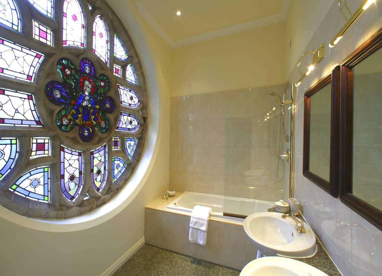 Magnolia suite bathroom with stained glass window at Ashdown Park Hotel