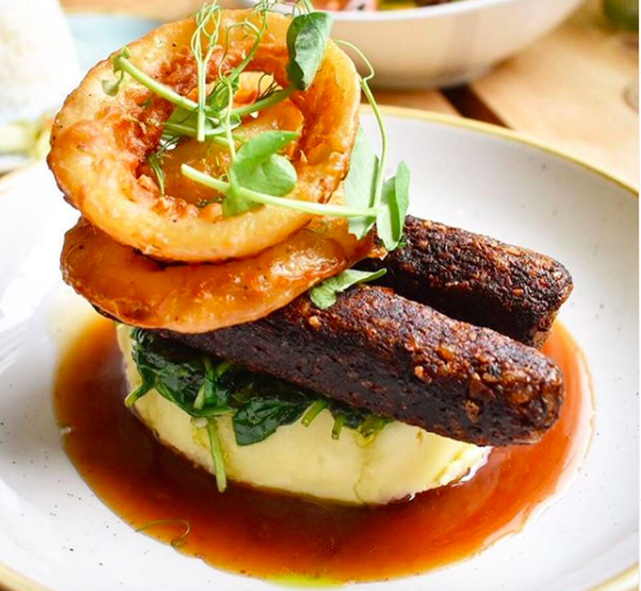 Smoked Mushroom and chestnut sausages on mushroom mash and wilted spinach, served with beer battered onion rings