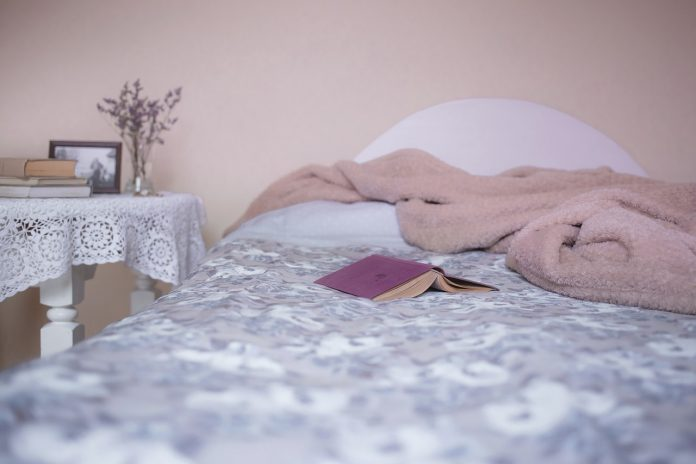 bed with a book and a cover