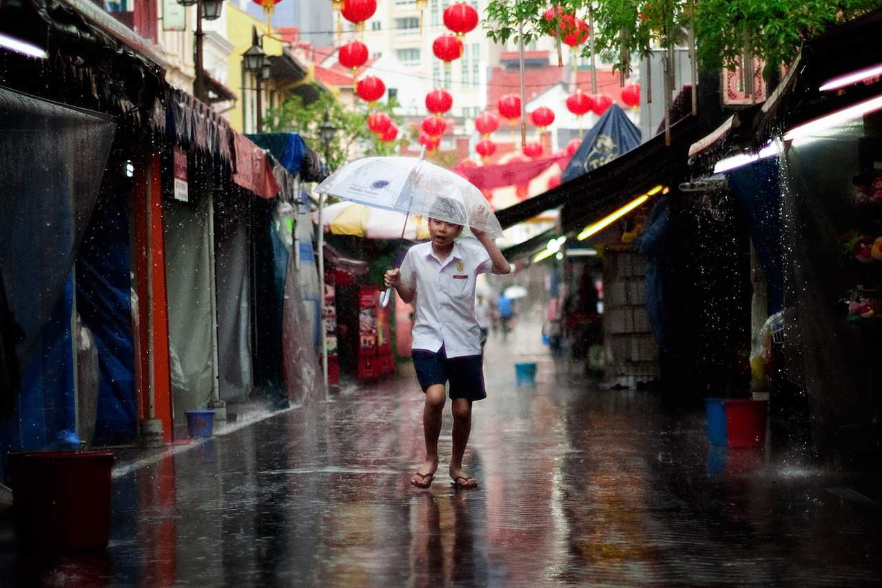 boy with the umbrella in pagoda street singapore