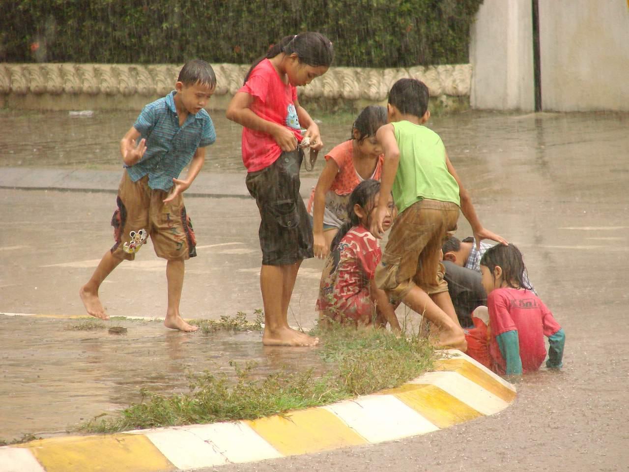 children play in monsoon downpour pakse laos