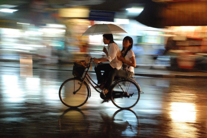 couple on the bycicle under the rain in hanoi vietnam