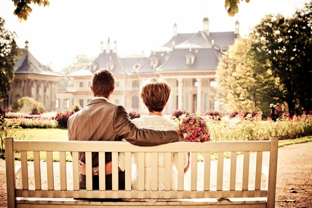 couple sitting in front of manor house