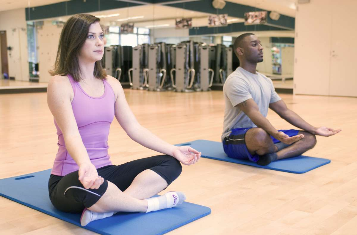 A man and woman practicing yoga in a fitness center